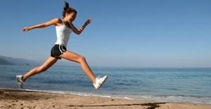 Happy girl running alone on the beach